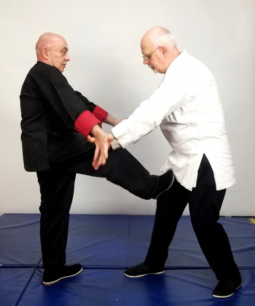 Low, knee-kick from overhand clear out after a shirt grab.